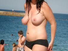 Brune à la plage fait du seins nus