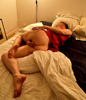 Elle se caresse la chatte sur le lit